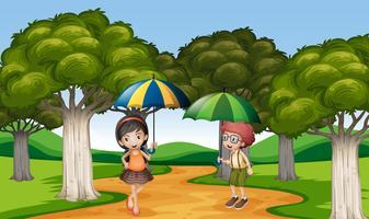 Två barn med paraply i parken