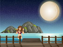 Linda mulher a nadar no oceano à noite