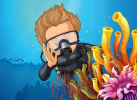 Scuba diver diving behind coral reef