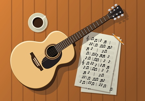 Guitarra, muebles y café en una mesa de madera