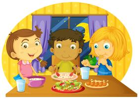 Drei Kinder, die Mahlzeit auf dem Tisch haben