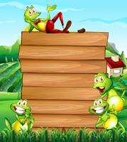 Wooden board and frogs in the field