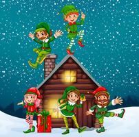 Cinco elfos en la cabaña de madera en la noche de navidad