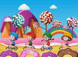 Kinder fahren Fahrrad am Strand voller Süßigkeiten