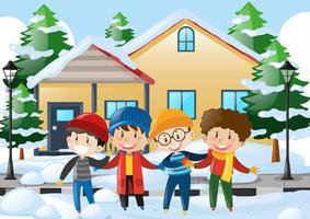 Cuatro niños parados en la carretera cubiertos de nieve.