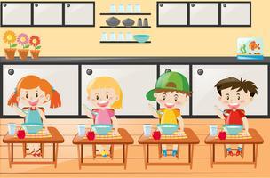 Cuatro niños comiendo en la cocina.