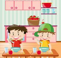 Chicos felices desayunando en la cocina