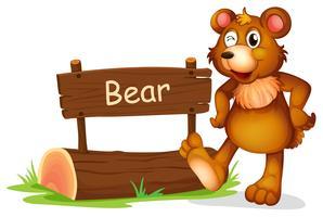 Un oso al lado de un cartel.