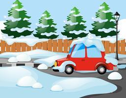 Escena del barrio con coche rojo cubierto de nieve.