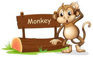 Un mono al lado de un cartel.