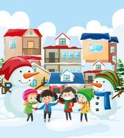 Bambini e pupazzo di neve nel villaggio
