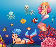 Två vackra sjöjungfrun och havsdjur under vattnet