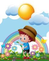 Liten pojke vattnar blommor i trädgården