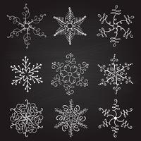 conjunto de nueve ilustración vectorial vintage Navidad copos de nieve en el fondo de la pizarra. Floritura caligráfica hecha a mano.