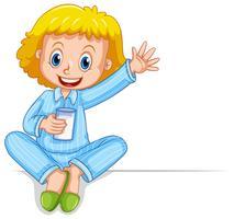 Liten flicka i pyjamas med glas mjölk