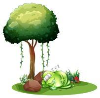 Un monstruo verde gordo que duerme bajo el árbol.