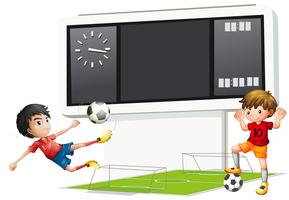 Two boys playing soccer with a scoreboard