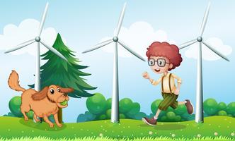 Un niño jugando con su perro cerca del molino de viento.