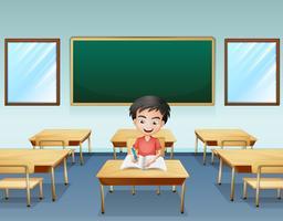 Um menino dentro de uma sala de aula com um tabuleiro vazio na parte de trás