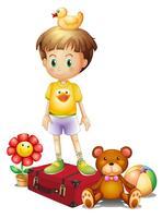 Un niño encima de la caja roja con sus diferentes juguetes.