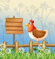 Uma galinha acima de uma cerca de madeira de frente para uma tabuleta de madeira