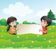 Ein Junge und ein Mädchen, die eine leere Pappe anhalten