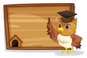 An owl wearing a graduation cap beside a wooden board