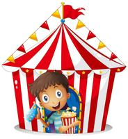 A young boy with a ticket and a popcorn near the tent