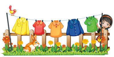 Eine Dame hängt ihre Kleider mit einem Vogel und einem Hasen im Garten auf
