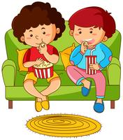 Two boys eating popcorn on sofa