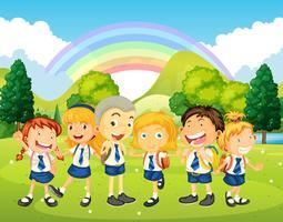 Niños en uniforme de pie en el parque.