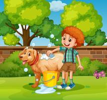 Niño dando baño de perro en el parque