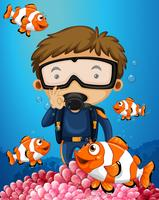 Man diving underwater with many clownfish