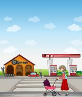 A mother walking along a garage and gasoline station