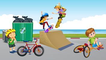 I bambini vanno in bicicletta e giocano a skateboard