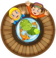 Moslemischer Junge und Mädchen am Fischteich