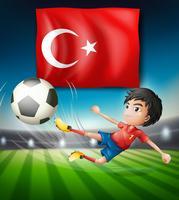 Ragazzo che dà dei calci ad un pallone da calcio davanti alla bandiera turca