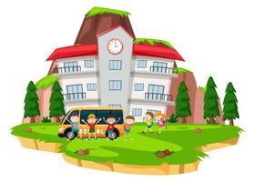 Niños jugando en el césped de la escuela.