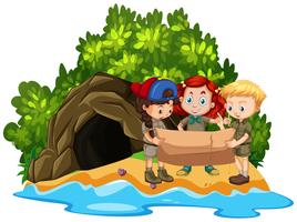Three kids looking at map in front of cave on island
