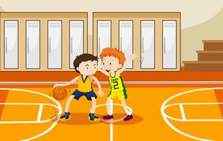 Two boys playing basketball in the gym