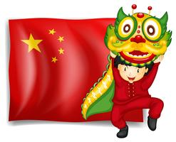 A boy doing the dragon dance in front of the flag of China