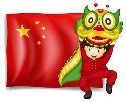 Een jongen die de drakendans voor de vlag van China doet