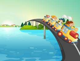 Kinderen rijden met de trein over de brug