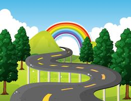 Park scene with road and rainbow in background