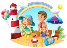 En familj på stranden med en fyr