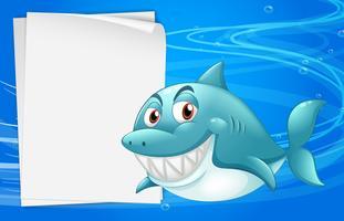 Un tiburón con un papel vacío debajo del mar.