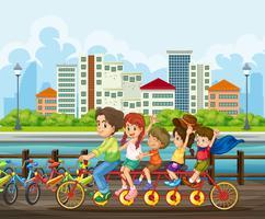 Una familia montando bicicleta tandem en el parque