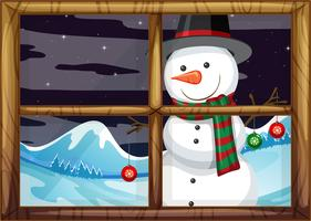 Een sneeuwpop buiten het raam