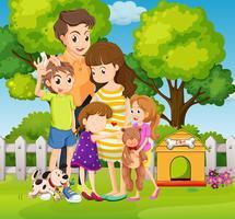 Härlig familj med tre barn och hund i trädgården
