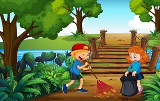 Dos niños limpiando hojas en el parque